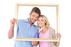 Attractive young couple holding picture frame Stock Image