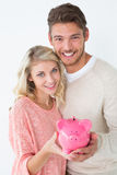 Attractive young couple holding piggybank Royalty Free Stock Photo