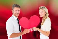 Attractive young couple holding red heart Royalty Free Stock Photos