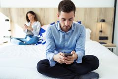 Attractive young couple ignoring each other using phone after an argument while sitting on bed at hotel room stock photo