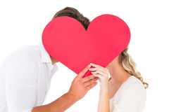 Attractive young couple kissing behind large heart Royalty Free Stock Photos