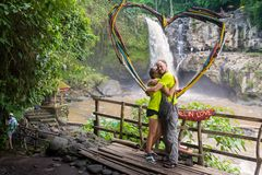 Attractive young couple kissing under jungle waterfall stock images