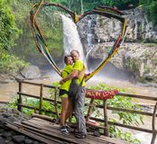 Attractive young couple kissing under jungle waterfall stock image