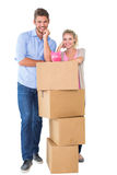 Attractive young couple leaning on boxes with piggy bank Stock Photography