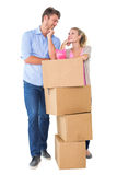 Attractive young couple leaning on boxes with piggy bank Stock Photos