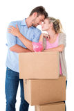 Attractive young couple leaning on boxes with piggy bank Royalty Free Stock Image
