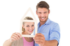 Attractive young couple looking through house outline Royalty Free Stock Photography