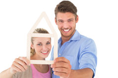 Attractive young couple looking through house outline Stock Images