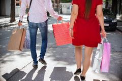 Romantic Young Couple In Love. Attractive Young Couple In Love walking in the city on a sunny day with shopping bags Royalty Free Stock Image