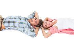 Attractive young couple lying smiling at camera. On white background Royalty Free Stock Photos