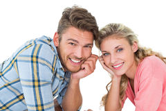 Attractive young couple lying and smiling at camera. On white background Royalty Free Stock Photography