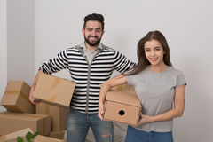 Attractive young couple is moving, smiling and holding boxes while standing among unpacked boxes. Royalty Free Stock Photo