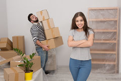 Attractive young couple is moving, smiling while standing among cardboard boxes. Stock Photos
