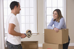 Attractive Young Couple Packing And Smiling. An attractive young couple is in the process of packing for a move. Horizontal shot Royalty Free Stock Photo