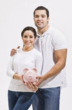 Attractive Young Couple with Piggy Bank Royalty Free Stock Photography