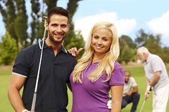 Attractive young couple ready for golfing. Attractive young couple standing and embracing at golf course royalty free stock images