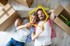 Attractive young couple relax between boxes on floor at new apartment stock images