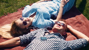 Attractive young couple relaxing in the summer sun. Lying on their backs on a rug outdoors on the grass head to head with the young man listening to music stock video footage