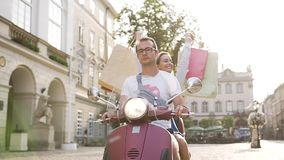 Attractive young couple riding on scooter on the urban street and happy woman raised hands with purchases stock footage