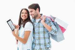 Attractive young couple with shopping bags and tablet pc Stock Image