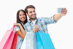 Attractive young couple with shopping bags taking a selfie Royalty Free Stock Image