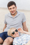 Attractive young couple sitting on beach at summer. Stock Photos
