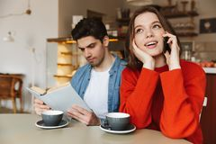 Attractive young couple sitting at a cafe table together Royalty Free Stock Photography