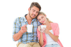 Attractive young couple sitting holding mugs Royalty Free Stock Images