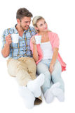 Attractive young couple sitting holding mugs Stock Photos