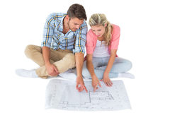 Attractive young couple sitting looking at blueprint Stock Photo