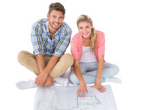 Attractive young couple sitting looking at blueprint Royalty Free Stock Photography