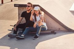 Young trendy couple are sitting at sunny skatepark with their longboards stock photography