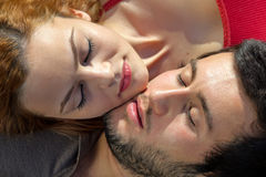 Attractive young couple sleeping. Head to head, closeup cropped portrait of their peaceful faces Stock Photos