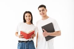 Attractive young couple standing isolated over white. Background, holding books stock photography