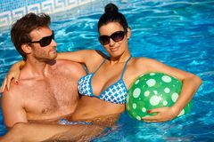 Attractive young couple in swimming pool. Attractive young couple having fun in swimming pool royalty free stock images