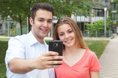 Attractive young couple taking a selfie with mobile phone Royalty Free Stock Photography
