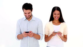Attractive young couple texting on phones
