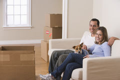Attractive Young Couple and Their Dog. A young couple and their dog are sitting on a couch in a living room. Moving boxes are arranged on the floor around them Stock Images