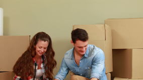 Attractive young couple unpacking boxes stock footage