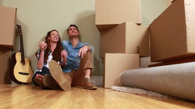 Attractive young couple unpacking boxes. In their living room stock footage