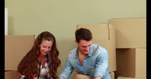 Attractive young couple unpacking boxes stock video footage