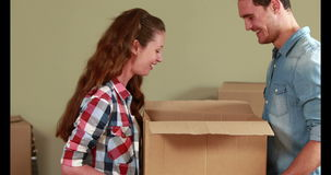 Attractive young couple unpacking boxes stock video