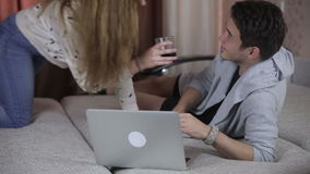 Attractive young couple using laptop, lying on sofa. stock video footage