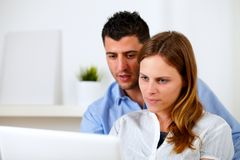 Attractive young couple using laptop together. Portrait of a attractive young couple using laptop together at home indoor Stock Photography