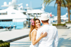 Attractive young couple walking alongside the marina in summer s. Attractive young couple walking alongside the marina with moored boats on a luxury waterfront Stock Photo