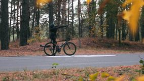 Attractive young cyclist in cycling clothes, black helmet and sports sunglasses doing `dab` pose in autumn forest. Happy handsome. Caucasian guy with road bike stock video footage