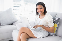 Attractive young dark haired woman in white clothes using a laptop Royalty Free Stock Photography