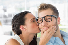 Attractive young designer getting a kiss from a co worker Stock Photo