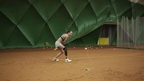 Attractive young disabled woman exercising. She kicks the ball on the elastic band that comes back. Training. Slow. Motion stock footage