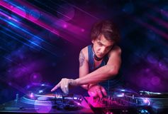 Young DJ playing on turntables with color light effects. Attractive young DJ playing on turntables with color light effects Royalty Free Stock Image